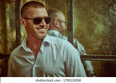 Portrait of a smiling wealthy mature man in a white shirt and modern sunglasses in a luxury apartment. Male beauty, fashion. Optics, sunglasses for men.