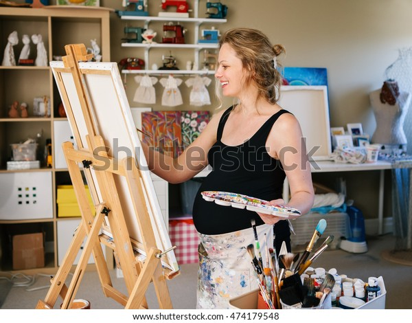 Portrait of smiling white Caucasian young pregnant woman drawing painting standing at easel in home studio, art mental therapy, healthy happy lifestyle concept
