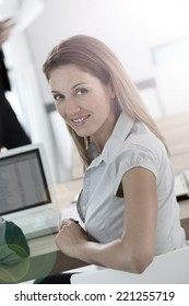 Portrait of smiling woman attending business preesentation