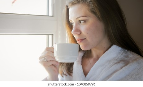Portrait of smiling woman in bathrobe looking out of window and drinking tea