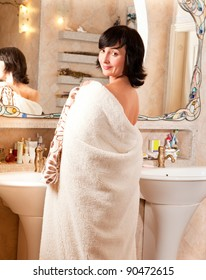Portrait of smiling woman in bathroom by the mirror wrapped in mantle
