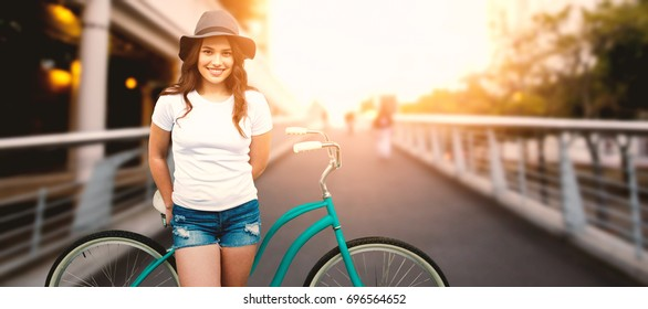 Portrait of smiling woman with bicycle against footbridge against sky in city