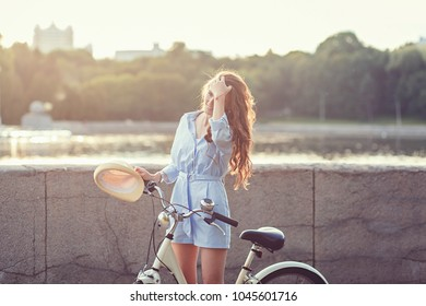portrait of a smiling woman with a bicycle at sunset