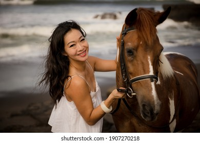 Portrait of smiling woman and brown horse. Asian woman cuddling horse. Romantic concept. Love to animals. Nature concept. Selected focus. Bali, Indonesia