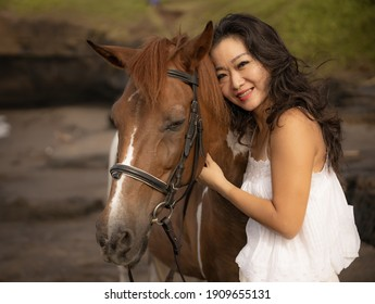 Portrait of smiling woman and brown horse. Asian woman hugging horse. Romantic concept. Love to animals. Nature concept. Bali, Indonesia