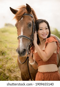 Portrait of smiling woman and brown horse. Asian woman hugging horse. Romantic concept. Positive emotions. Love to animals. Nature concept. Bali, Indonesia
