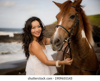 Portrait of smiling woman and brown horse. Asian woman cuddling horse. Romantic concept. Human and animals relationship. Nature concept. Selected focus. Bali, Indonesia