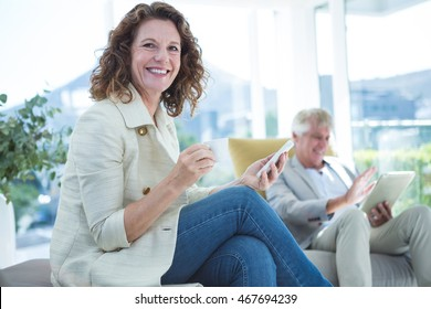 Portrait of smiling woman by man holding mobile phone on sofa at home