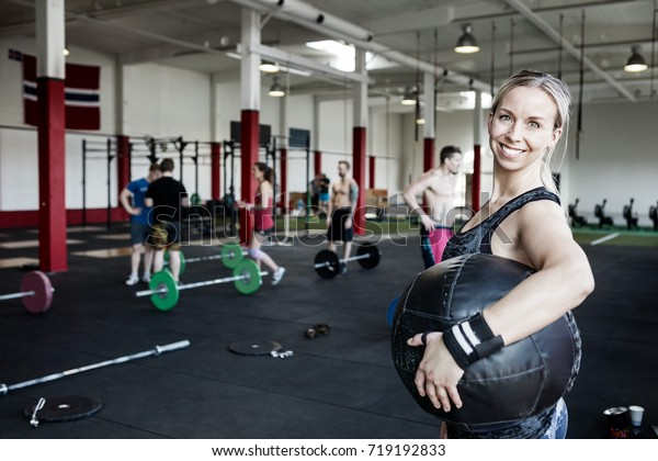 Portrait Of Smiling Woman Carrying Medicine Ball