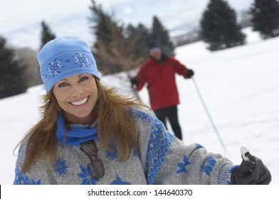 Portrait of smiling woman cross country skiing with blurred man in the background