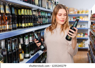 Portrait of smiling  woman customer buying bottle of beer in the supermarket