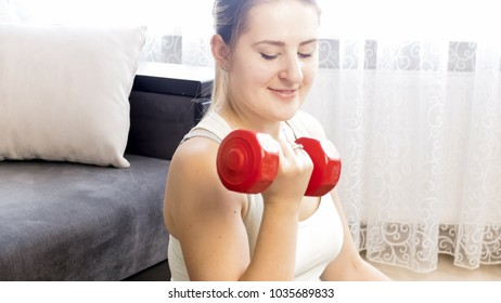 Portrait of smiling woman doing exercise with dumbbells at home