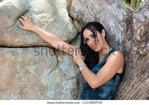 portrait of a smiling woman in a dress on a background of natural stone and dried wood