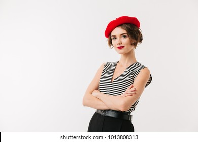 Portrait of a smiling woman dressed in red beret standing with arms folded isolated over white background