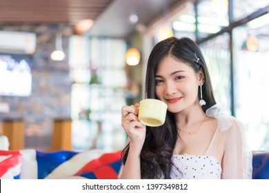 Portrait of smiling woman drinking coffee at vintage cafe.