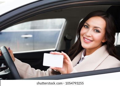 Portrait of smiling woman driver holding a white blank business card