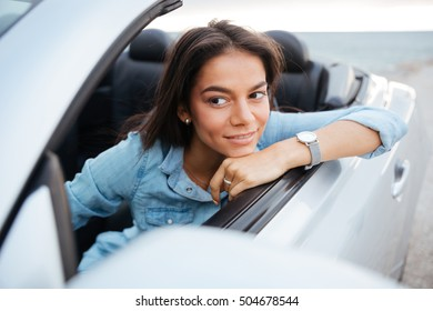 Portrait of smiling woman driving convertible car on beach