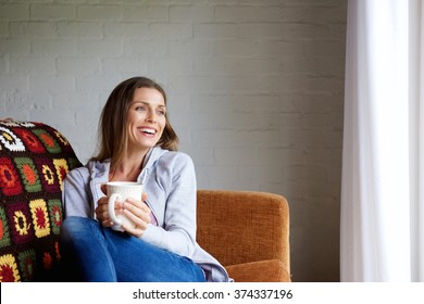 Portrait of a smiling woman enjoying cup of tea at home