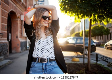 Portrait of smiling woman in the evening. Happy young girl walking around town, portrait on the city background.