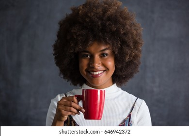Portrait of smiling woman with frizzy hair holding coffee mug against wall