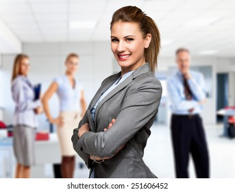 Portrait of a smiling woman in front of a group of business people