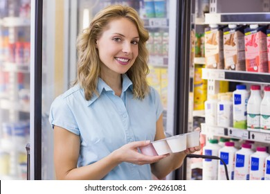 Portrait of a smiling woman having on her hands a fresh yogurt in supermarket