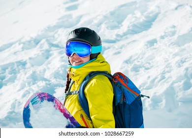 Portrait of smiling woman in helmet and with snowboard on background of snowy landscape