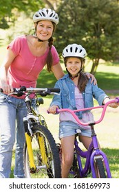 Portrait of a smiling woman with her daughter riding bicycles