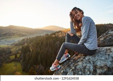 portrait of smiling woman hiker sitting on edge of cliff against background of sunrise