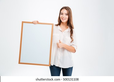 Portrait of a smiling woman holding blank board and showing thumb up isolated on a white background