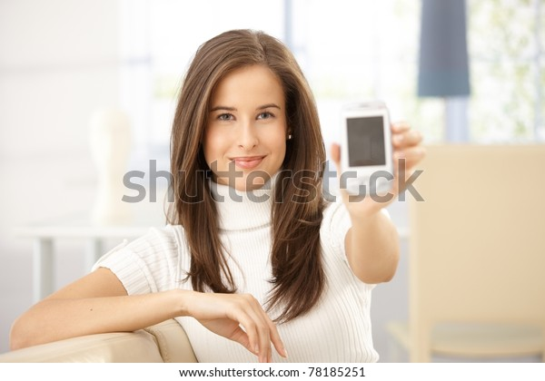 Portrait of smiling woman holding cellphone up to camera.?