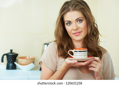 Portrait of smiling  woman holding coffee cup at the kitchen interior. Close up smiling female face.