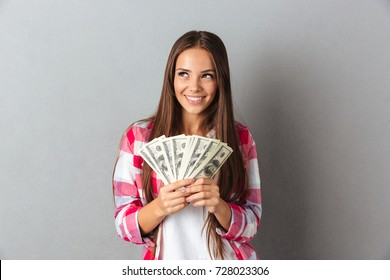 Portrait of smiling woman holding dollars, over gray background