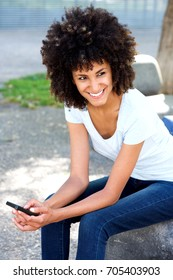 Portrait of smiling woman holding mobile phone in urban park