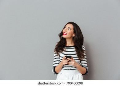 Portrait of a smiling woman holding mobile phone and looking away at copy space isolated over gray background