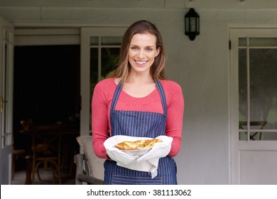 Portrait of a smiling woman holding pie in a pan