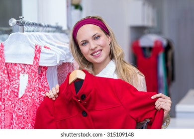 Portrait of smiling woman holding red coat in clothing store