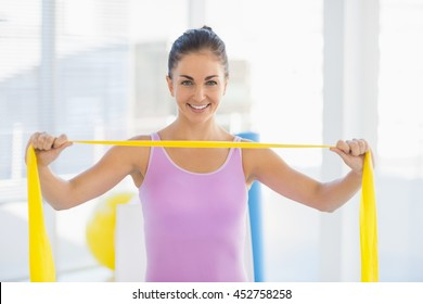 411150f63f1 Portrait of smiling woman holding resistance band at fitness studio
