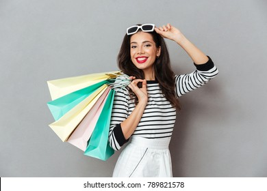Portrait of a smiling woman holding shopping bags and looking at camera isolated over gray background