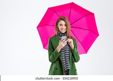 Portrait of a smiling woman holding smartphone under umbrella and looking at camera isolated on a white background