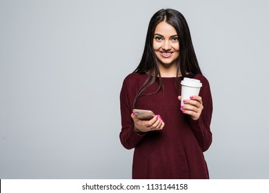 Portrait of smiling woman holding takeaway coffee cup and using mobile phone isolated over gray background