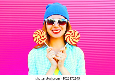 portrait smiling woman holds a lollipop on stick on pink background