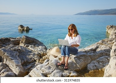Portrait of smiling woman with laptop sitting by the sea and working online. Middle age female writing her presentation on computer.