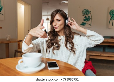 Portrait of a smiling woman listening to music with mobile phone and pointing finger at camera while sitting at the table in a cafe indoors and drinking coffee