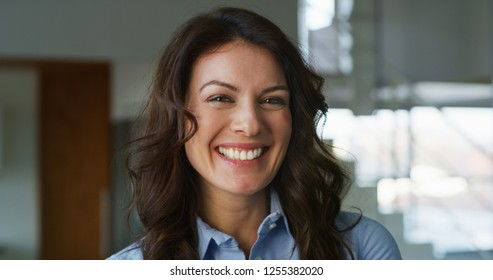 Portrait of a smiling woman in living room in slow motion. Concept of femininity, woman, mother