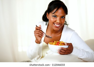Portrait of a smiling woman looking at you and having breakfast while is sitting on sofa at home indoor. with copyspace