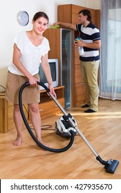 Portrait of smiling woman and man cleaning flat together