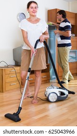 Portrait of smiling woman and man cleaning flat after work