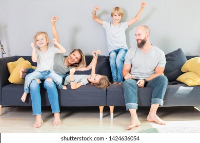 Portrait of smiling woman and man having fun and playing around with kids, while sitting on sofa together, in living room at home