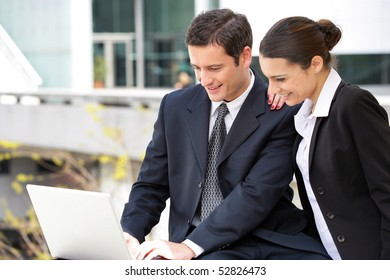 Portrait of smiling woman and man with a laptop computer